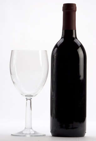 A Bottle of red wine with a wine glass on a plain background Stock Photo