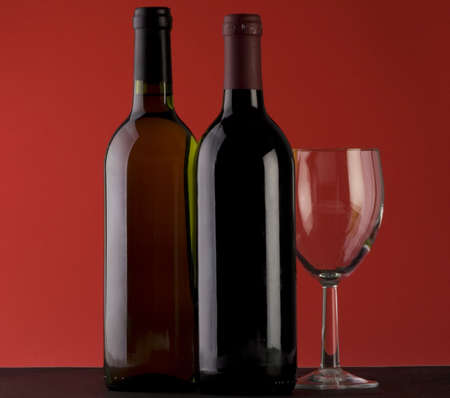 Two Bottles of red wine with a wine glass on a plain background