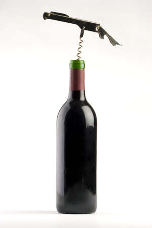 A Bottle of red wine with a corkscrew on a plain background