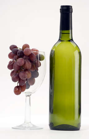 A Bottle of white wine with grapes on a plain background