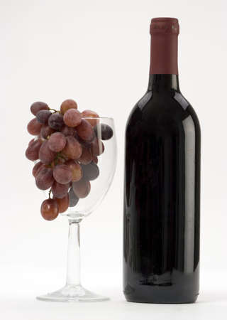 redwine: A Bottle of red wine with grapes on a plain background