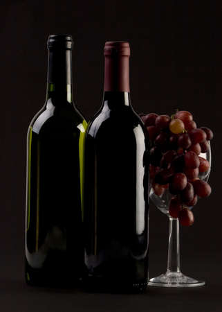 Two Bottles of red wine with grapes on a plain background