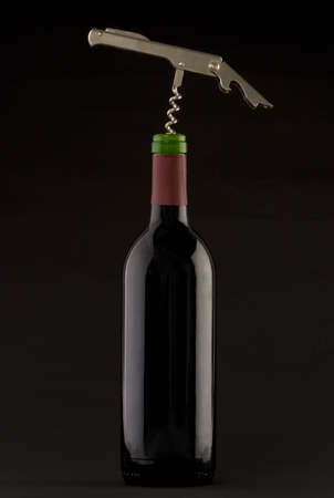 redwine: A Bottle of red wine with a corkscrew on a plain background