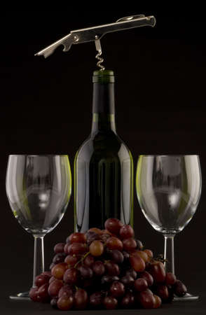 redwine: A Bottle of white wine with glasses,corkscrew and grapes on a plain background