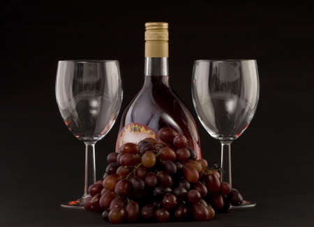 A Bottle of rose wine with grapes and wine glasses on a plain background Stock Photo - 2038407