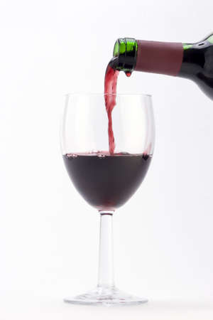 A glass of red wine being poured against a plain background.