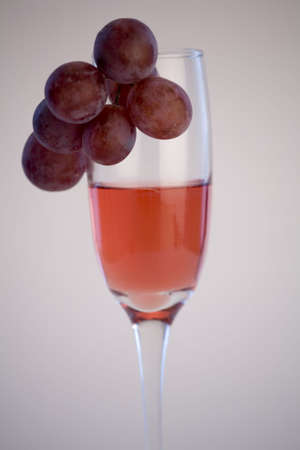 A glass of rose wine with grapes against a plain background. Stock Photo - 2119617