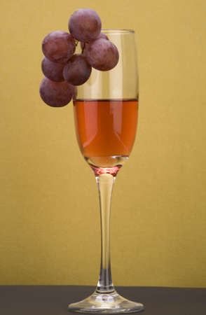 A glass of rose wine with grapes against a plain background. Stock Photo - 2119621