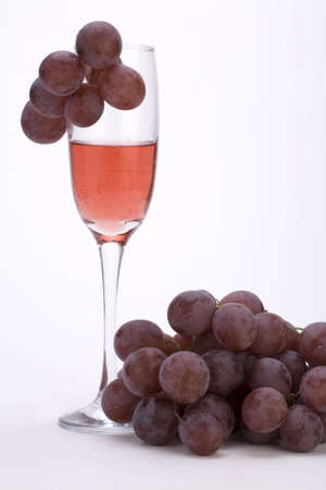 A glass of rose wine with grapes against a plain background. Stock Photo - 2242083