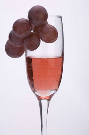 A glass of rose wine with grapes against a plain background. Stock Photo - 2242074