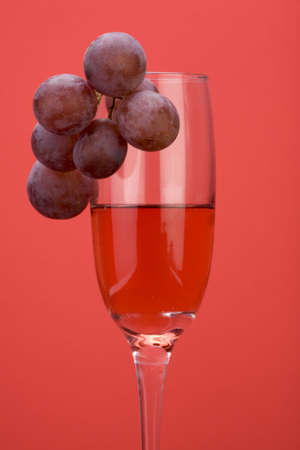 A glass of rose wine with grapes against a plain background. Stock Photo - 2242095