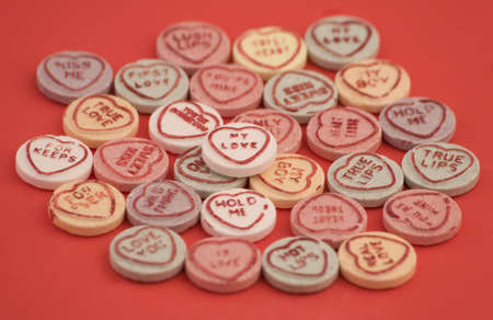 colorfuls: Love heart candy isolated on a Red Background. Stock Photo