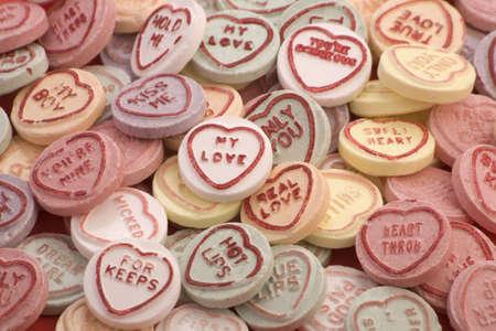 süssigkeiten: Love Herzen candy isoliert auf einem roten Hintergrund.