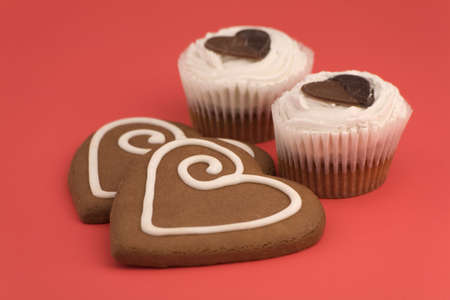 Love heart Cookies and cakes isolated on a Red Background. photo