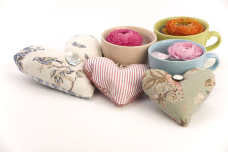 Three cups with flower heads and love heart cushions on a plain background.