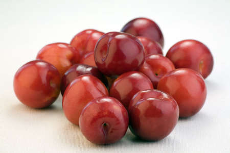 Multiple red plums against a white linen background. Stock Photo - 2528538