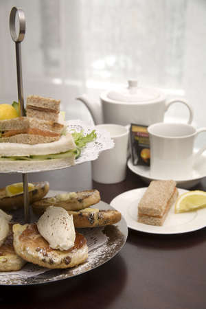 An arrangement of sandwiches and scones for afternoon tea Фото со стока