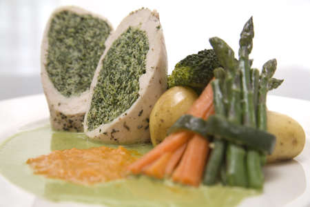 A dish of Stuffed Chicken breast and sauce with vegetables  Фото со стока