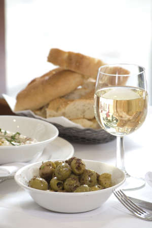 Some white Wine with Bread and a bowl of Olives