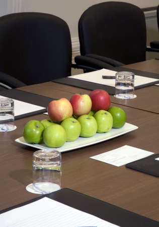 Boardroom place setting with a bowl of apples. Stock Photo