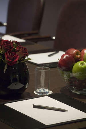 A blank corporate display book with a bowl of apples and red roses.