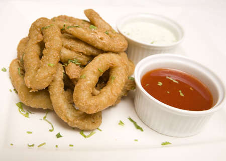 A dish of Fried Onion rings with ketchup and mayonnaise.
