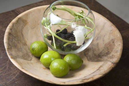 blackberry fruit: An interior image of a round glass fruit bowl with lemons and flowers.