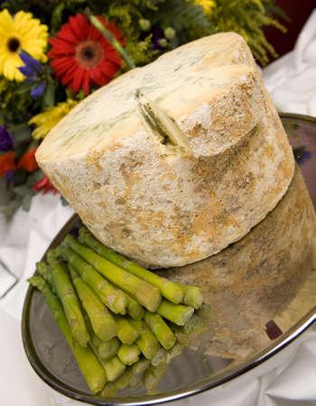 A whole Stilton cheese with asparagus spears.