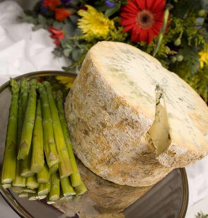 stilton: A whole Stilton cheese with asparagus spears.