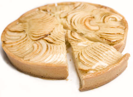 An Apple pie with a slice cut out isolated. photo