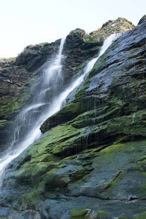 flowing water: A cascade of flowing water from a waterfall.