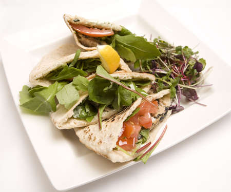 Pitta bread filled with a tuna salad on a white plate. Stock Photo