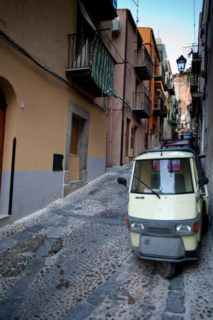A narrow Cefalu street with three wheeled van in Sicily