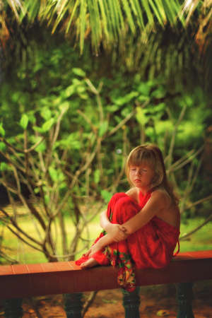 stoop: A girl sits in a tropical Paradise and dreams Stock Photo