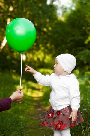 curiously: little girl curiously shows a balloon in summer on nature Stock Photo
