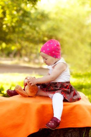 enjoys: little girl enjoys playing with Teddy Bear in summer