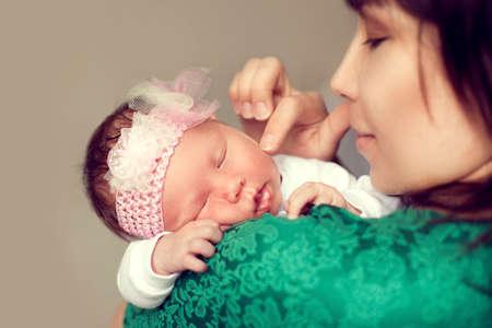 personas abrazadas: Madre asiática joven que sostiene el hombro del bebé, que está durmiendo y suavemente acaricia la mejilla con un dedo