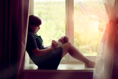 hugging knees: young woman mother sitting at the window with a newborn baby and holds his hands and looks tenderly at her
