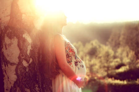 Pregnant woman with long hair standing in the summer, against a tree in the rays of the setting sun and holding his stomach with his hands, enjoying the nature