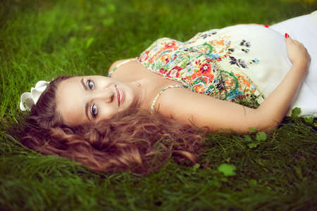 looking directly at camera: European beautiful pregnant woman in a floral sundress in the summer lies on green grass and looking directly at the camera, supports abdomen with hands Stock Photo