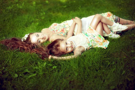 stay in green: beautiful girl with long hair lying next to his pregnant mother in the summer on the green grass. Stay for the weekend Stock Photo