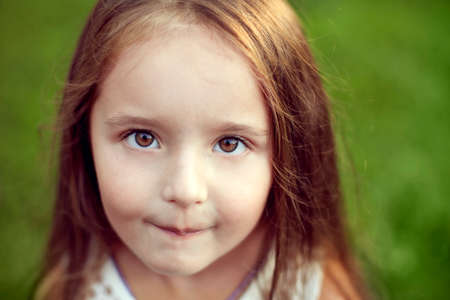hazel eyes: beautiful white girl with long hair and hazel big eyes looking straight at the camera and smiling in summer, outdoors, close-up Stock Photo