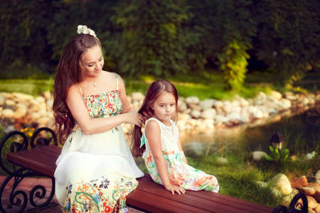 womanhood: Beautiful white European woman combing long hair of his daughter sitting outdoors near the pond. Nice girl sits quietly and loves his mother