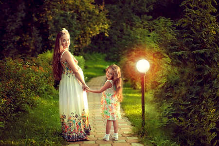 Beautiful pregnant woman in the summer is walking with my daughter in a magical forest, stopped on the path and turned around, holding hands. The light of a lantern. Mom and girl. Stock Photo
