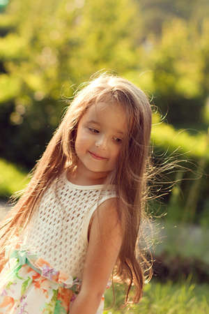 coy: beautiful baby girl summer evening having fun in the sunlight, the wind ruffles your hair. The coy smile of the model Stock Photo