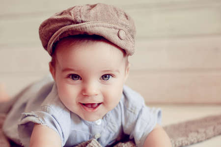 Adorable happy baby boy in a bright room. The baby in the hat smiling looking at camera. Retro style Stock Photo