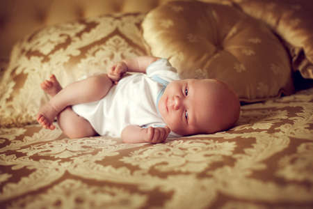 newborn healthy baby 2 weeks old is lying in a posh bedroom on the parents bed and smiles. A small child in the comfort of your room