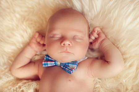 Sleeping newborn baby lying with the bow tie on a white fur in his arms. Little gentleman resting after a hard day Standard-Bild