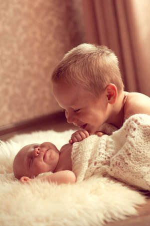 communicates: White European boy 5 years communicates with her newborn brother in a cozy room. Family values, good attitude to children Stock Photo