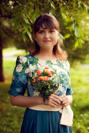 Young beautiful woman in floral dress posing in Park with a bouquet of flowers, on green background summer nature. Standard-Bild